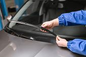 Technician Is Changing Windscreen Wipers On A Car Station poster