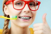 Dentist And Orthodontist Concept. Young Woman With Blue Braces Cleaning And Brushing Teeth Using Man poster