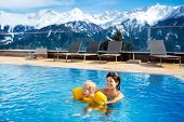 Mother And Baby Play In Outdoor Swimming Pool Of Luxury Spa Alpine Resort In Alps Mountains, Austria poster