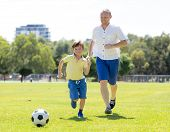 Young Happy Father And Excited 7 Or 8 Years Old Son Playing Together Soccer Football On City Park Ga poster