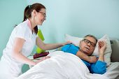 Постер, плакат: Nice Smiling Nurse Looking At Patient Who Sleeping And Dreaming