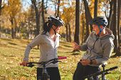 Happy Young Couple Having Fun Riding A Bicycle On Sunny Autumn Day In The Park. Two People Are Talki poster