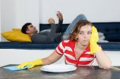 Frustrated Woman Cleaning Room With Lazy Man Relaxing On Couch At Home poster