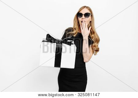 poster of Happy Excited Young Girl In Black Dress Holding Black Friday Gifts, On White Background Holding Gift