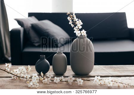 poster of Minimalistic home decor on rustic coffee table over black sofa with cushions. Grey vases and spring