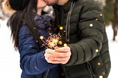 Happy Young Romantic Couple Have Fun Outdoors In Winter With Bengal Lights. Two Lovers Are Hugging A poster