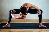 A Man In Dark Sportswear Practicing Yoga On A Dark Background. Asana On The Floor On Yoga Mats. The  poster