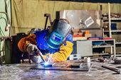 Welder At Work. Worker Welds Metal Parts. Welding Process, Sparks, Flame, Smoke. Plant For The Produ poster