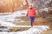 Young Slim Woman Jogging In Winter Park poster