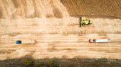 Aerial View Of A Combine That Unloads Grain From Its Grain Compartment Into A Truck Van. One Truck D poster