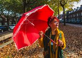 A Charming Asian Attractive Freaky Woman Of Seventy With A Red Polka Dot Umbrella Walks Through The  poster