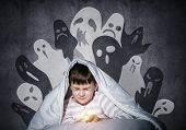 Frightened Child With Flashlight Hiding Under Blanket. Scared Kid With Closed Eyes Lying In Bed At H poster