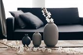 Minimalistic home decor on rustic coffee table over black sofa with cushions. Grey vases and spring  poster