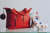 Fashion Trend Pair Of Stylish Sneakers And Big Red Handbag On Shelf In A Store, Shop. Fall, Autumn S poster
