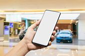 Mockup Image Of Hand Holding Blank Screen Mobile Smart Phone With Blurred Background Of New Cars Dis poster