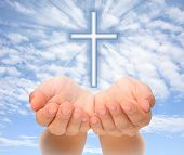 stock photo of hand god  - Hands holding Christian cross with light beams over sky - JPG