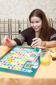Happy Caucasian Young Female Playing Board Games In Domestic Room poster