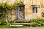 stock photo of english cottage garden  - Ancient oak front door to cottage in Stanton in Cotswold or Cotswolds district of southern England in the autumn - JPG