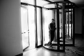 foto of late 20s  - Young man in his twenties walks through a revolving doorway entrance - JPG