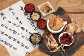 foto of qi  - Traditional chinese herbal medicine selection with mandarin calligraphy on rice paper over oak - JPG