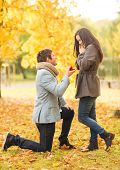 holidays, love, couple, relationship and dating concept - kneeled man proposing to a woman in the au