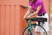 pic of riding-crop  - cropped view of business woman locking padlock to her bike - JPG
