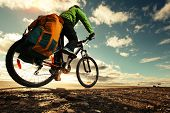 picture of exercise bike  - Bicycle tourist with loaded bike riding on an empty road - JPG