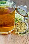picture of meadowsweet  - Metal sieve with dried flowers of meadowsweet a bouquet of fresh flowers of meadowsweet tea in glass mug on a background of wooden boards - JPG