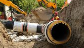 picture of excavator  - Excavator laying huge pipe in a trench - JPG