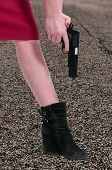 stock photo of gun shot wound  - A beautiful woman shooting herself in the foot - JPG