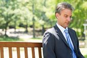 Mature businessman looking down while relaxing on park bench