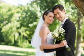stock photo of half-dressed  - Portrait of loving newly wed couple with head to head standing in garden - JPG
