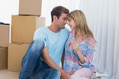 Happy loving young couple holding new house key against cardboard boxes