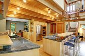 pic of stool  - View of shiny kitchen with steel appliances light wooden cabinets and ceiling beams - JPG