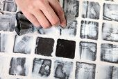 stock photo of grout  - a hand of a worker applies grout at grey tiles - JPG