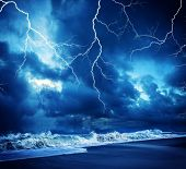 stock photo of flashing  - Lightning flashes across the beach from a powerful storm - JPG