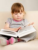 Little girl reading a book sitting on the couch