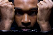foto of racial discrimination  - close up portrait of hand cuffed black man - JPG
