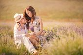 image of lavender field  - Young beautiful sensual couple kissing outdoors in windy weather in the summer on a lavender field - JPG