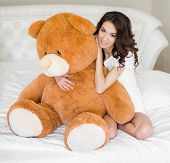 Pretty girl lying on the bed with a teddy bear pic.