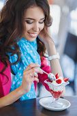 stock photo of sms  - young beautiful woman eating a dessert - JPG