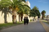 picture of rabbi  - Two rabbies walking along wall of old town Jerusalem Israel - JPG
