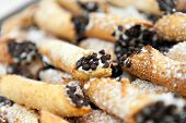 image of confectioners  - Tray full of freshly filled cannolis with chocolate chips and confectioners sugar. Shallow depth of field.