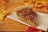 stock photo of pecan  - A slice of pecan pie with autumn leaves on a rustic wooden counter - JPG