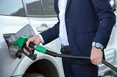 picture of fuel economy  - Young businessman refueling car tank at fuel station - JPG