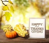 stock photo of thanksgiving  - Happy Thanksgiving message card with pumpkins over yellow leaves - JPG