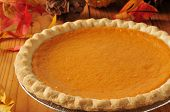 pic of gourds  - Closeup of a pumpkin pie on a table with autumn leaves and pine cones - JPG