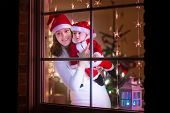 picture of santa baby  - Young mother in red Christmas hat and her baby boy dressed in Santa costume standing next to a window in a decorated living room celebrating Xmas with lights and tree - JPG