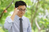 stock photo of hustler  - Asian businessman is thinking his work in the park