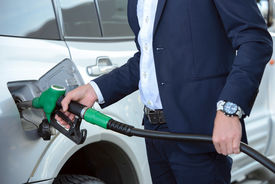 stock photo of fuel economy  - Young businessman refueling car tank at fuel station - JPG